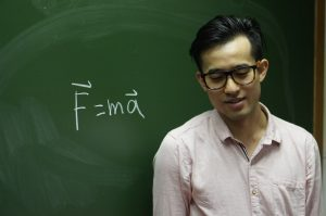 Hoi-Fung David Yu stands in front of a chalkboard which says F=ma.