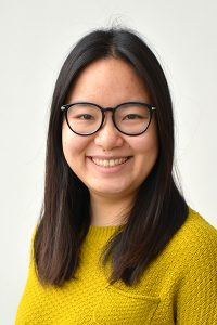 An image of Fei Xie with a yellow sweater and black glasses.